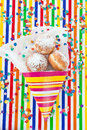 Fresh doughnuts in striped bag and confetti on colorful background Stock Photography
