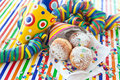 Fresh doughnuts in striped bag and confetti on colorful background Royalty Free Stock Image