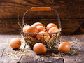 Fresh eggs in a basket on wooden table Stock Photography