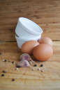 Fresh eggs paper and garlic for breakfast with white plates on wooden background Royalty Free Stock Photo