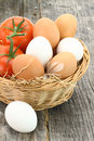 Fresh eggs and tomatoes in the basket Stock Photo