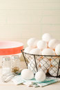 Fresh eggs in a wire basket several rest with vintage bowl and whisk accented with old fashioned salt and pepper shakers Stock Image