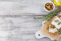 Fresh feta cheese with rosemary on white wooden serving board Royalty Free Stock Photo