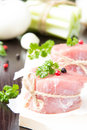 Fresh fillet of raw meat tied with twine on wooden desk with pep spices and herbs Stock Photos