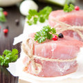 Fresh fillet of raw meat tied with twine on wooden desk with pep spices and herbs Stock Images