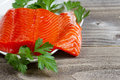 Fresh fillet of sockeye salmon with parsley closeup horizontal photo partially out plate on the side and rustic wood underneath Stock Photography