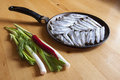 Fresh fish on an old frying pan the process of cooking near vegetables onions and peppers a wooden table Royalty Free Stock Photography