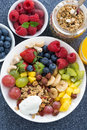 Fresh foods for a healthy breakfast berries fruits nuts and muesli vertical close up top view Royalty Free Stock Photos