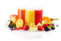 Fresh fruit with glasses of juice colourful arrangement including berries citrus and apples liquidised for a healthy start to Stock Images