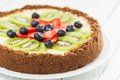 Fresh fruit pie cheesecake with kiwi blueberry and strawberry on a plate Stock Photo