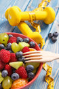 Fresh fruit salad with fork and centimeter with dumbbells, healthy lifestyle and nutrition concept Royalty Free Stock Photo