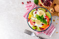 Fresh fruit salad with yogurt and walnuts in glass bowl on stone background. Royalty Free Stock Photo