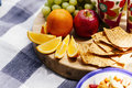 Fresh fruit and snacks on picnic blanket sitting wood chopping board Royalty Free Stock Image