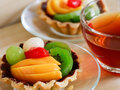 Fresh fruit tarts on wooden panel include kiwi lychee grapefruit strawburry peaches and a cup of herbal tea table Royalty Free Stock Images