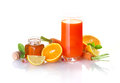 Fresh fruit and vegetable juice made from a blend of healthy honey citrus fruits carrots in a colourful still life on white Royalty Free Stock Images