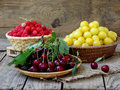 Fresh fruits and berries in the basket on wooden background Royalty Free Stock Photo