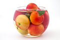 Fresh fruits in glass and juicy plums a of water on white background Stock Photo