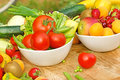 Fresh fruits and wegetables in bowls on the table Stock Image