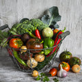 Fresh garden vegetables - broccoli, zucchini, eggplant, peppers, beets, tomatoes, onions, garlic - vintage metal basket Royalty Free Stock Photo