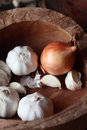 Fresh garlic cloves brown onion old rustic wooden bowl use as pungent flavouring cooking Stock Photography