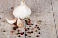 Fresh garlic and peppercorns on rustic wooden background Royalty Free Stock Photo