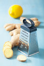Fresh ginger root and grater over blue metal Stock Photo