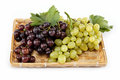 Fresh grape fruits with green leaves isolated. Royalty Free Stock Photos