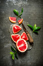 Fresh grapefruit with leaves and knife on a stone stand. Royalty Free Stock Photo