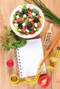 Fresh greek salad with vegetables, centimeter and notepad for writing notes, healthy nutrition and slimming concept Royalty Free Stock Photo