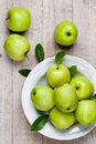 Fresh green apples in plate on wooden background Stock Photo