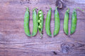 Fresh green beans of peas not like others pods on old wood Royalty Free Stock Photo