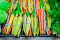 Fresh green cabbage, rainbow carrots and spinach in rubber bands at food store in America Royalty Free Stock Photo