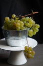 Fresh green grapes in metal bucket against dark background Stock Photo