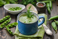 Fresh green pea soup with pea seeds and pea pods Royalty Free Stock Photo