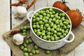 Fresh green peas in a bowl with tomatoes garlic and red pepper on the table wooden Stock Photos