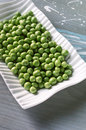 Fresh green peas peeled in a white plate on a wooden background selective focus Stock Photo