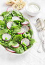 Fresh green peas, spinach and radish salad on a ceramic oval plate Royalty Free Stock Photo