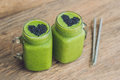 Fresh green smoothie with banana and spinach with heart of sesame seeds. Love for a healthy raw food concept Royalty Free Stock Photo