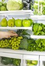 Fresh green vegetables and fruits in fridge. Woman takes the bunch of green grapes from the open refrigerator. Royalty Free Stock Photo