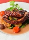 Fresh grilled octopus with olives potato tomatoes zucchini vegetable and parsley Stock Image
