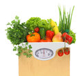 Fresh groceries in a paper bag with weight scale dial Royalty Free Stock Images