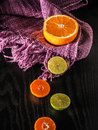 Fresh halves oranges and lime with copy space on color fabric an Royalty Free Stock Photo