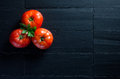 Fresh and health tomatoes over black slate closeup of three fleshy with copyspace Royalty Free Stock Photo