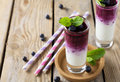 Fresh healthy blueberry smoothies in a glass with berries and mint leaves on a wooden stand. Royalty Free Stock Photo