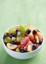 Fresh healthy fruit salad bowl of on green background Royalty Free Stock Images