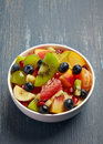Fresh healthy fruit salad bowl of on wooden background Royalty Free Stock Image