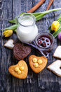 Fresh healthy milk and muffins delicious cookies with tulips jam cinnamon on a wooden background Royalty Free Stock Image