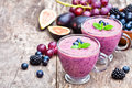 Fresh healthy pulpy cocktail with purple fruits and berries Stock Images