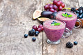 Fresh healthy pulpy cocktail with purple fruits and berries Stock Photos