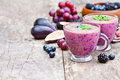 Fresh healthy pulpy cocktail with purple fruits and berries Royalty Free Stock Images